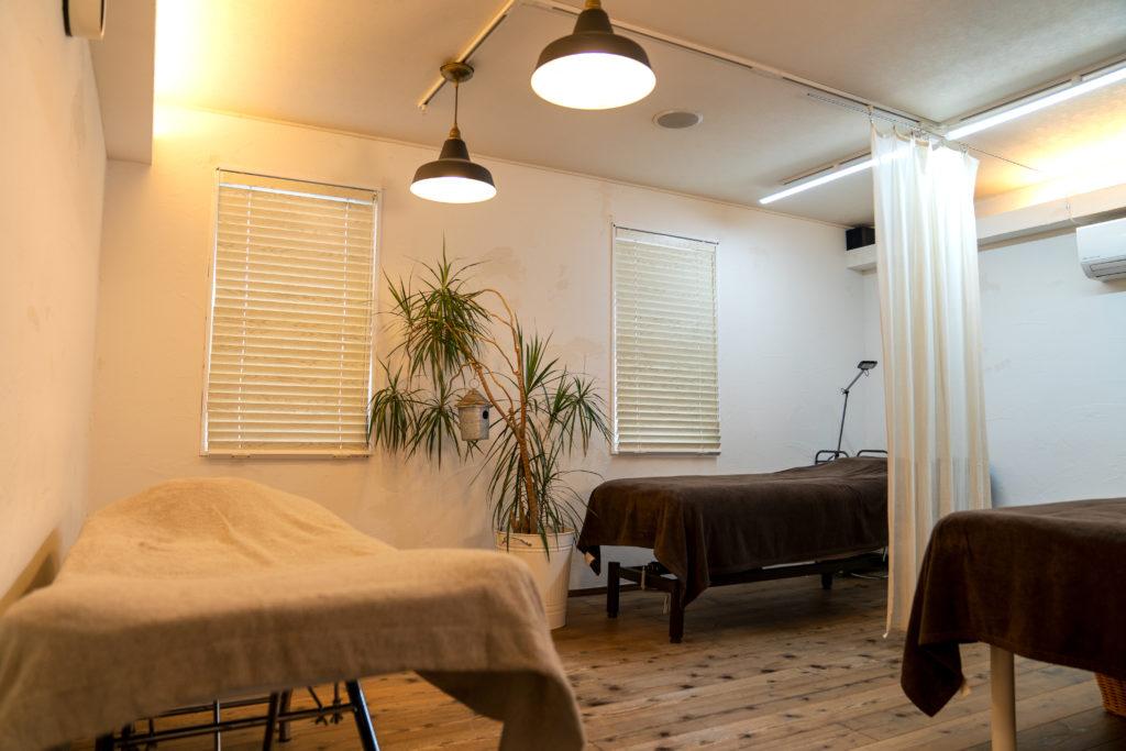 ウッドの床に大きな観葉植物があり、3台の施術台が大きな間隔をあけて置かれている、暖色のライトが灯るアイラッシュサロンメリッサの店内の様子
