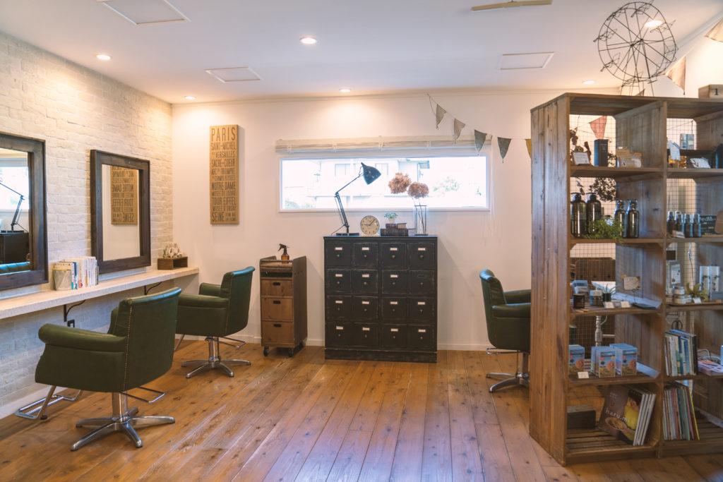 ウッドの床にアンティークの棚、横に長い窓から光がさしている、ウッドの枠の鏡の前には深いグリーンの皮製の椅子が並ぶミモザの店内