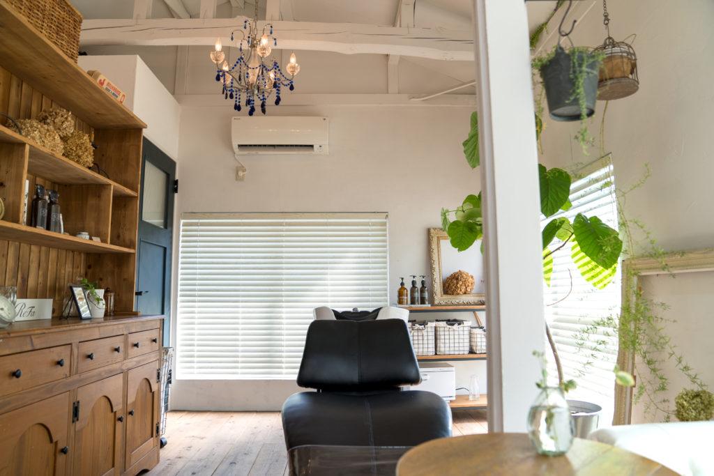ウッドの床にヴェンテージ感あるウッドの棚がある部屋に黒い革製のシャンプーチェアがある様子