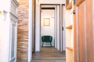 ウッドの床、奥の部屋には深い緑の皮製の背もたれ付きの椅子が置かれているolive pal店内の様子