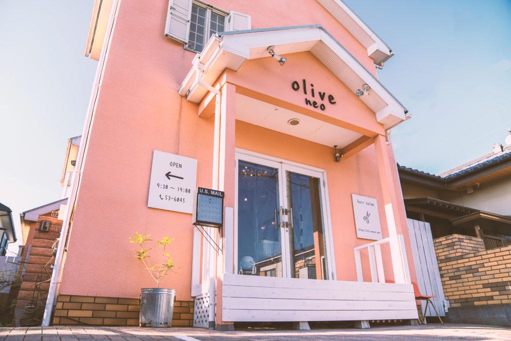 淡いピンクの壁に白い枠の大きなガラスのドアある。入り口にはアルミのバケツにグリーンが植えられている。美容室オリーブネオの外観。
