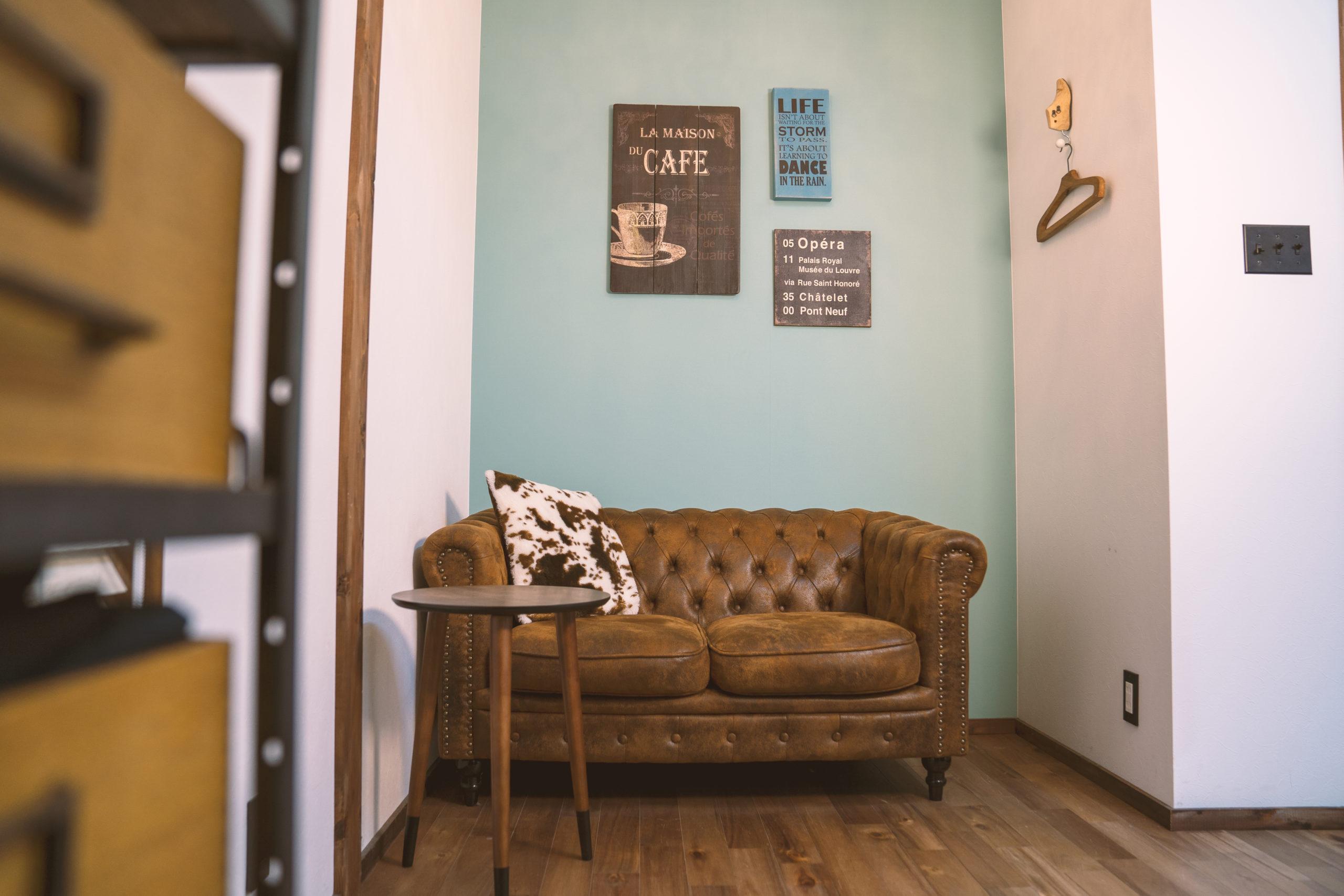 ウッドのフローリングにヴィンテージ感のあるブラウンの革製のソファがあり、淡いエメラルドグリーンの壁紙には木製の看板が飾られている店内の様子