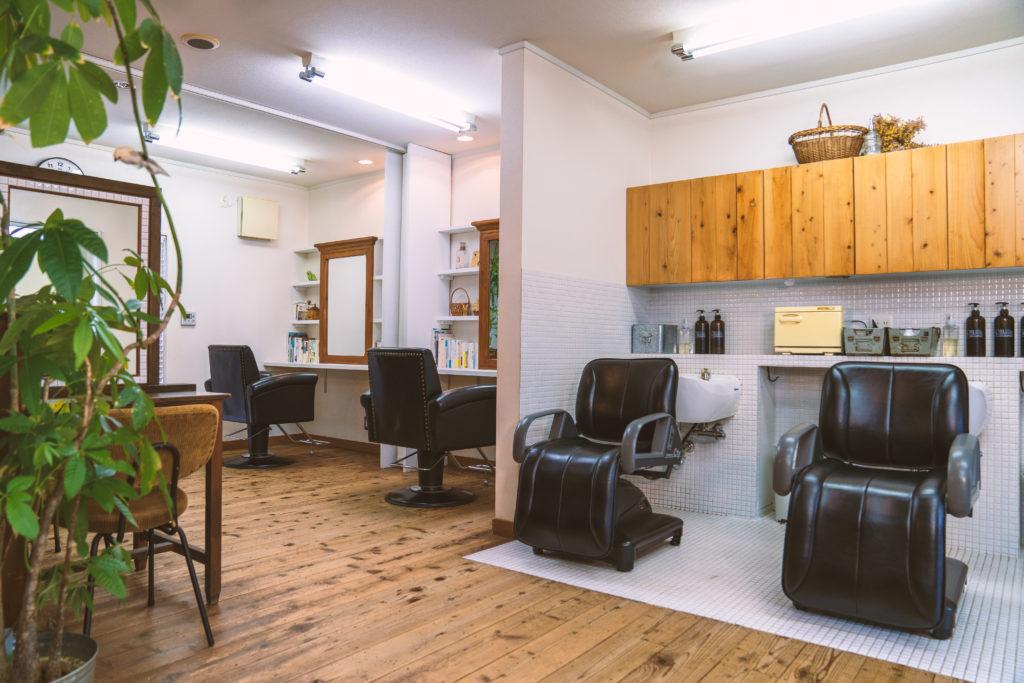 ウッドの床に黒い皮製のカット台が2台、シャンプー台が2台並んでいる美容室オリーブ店内の様子