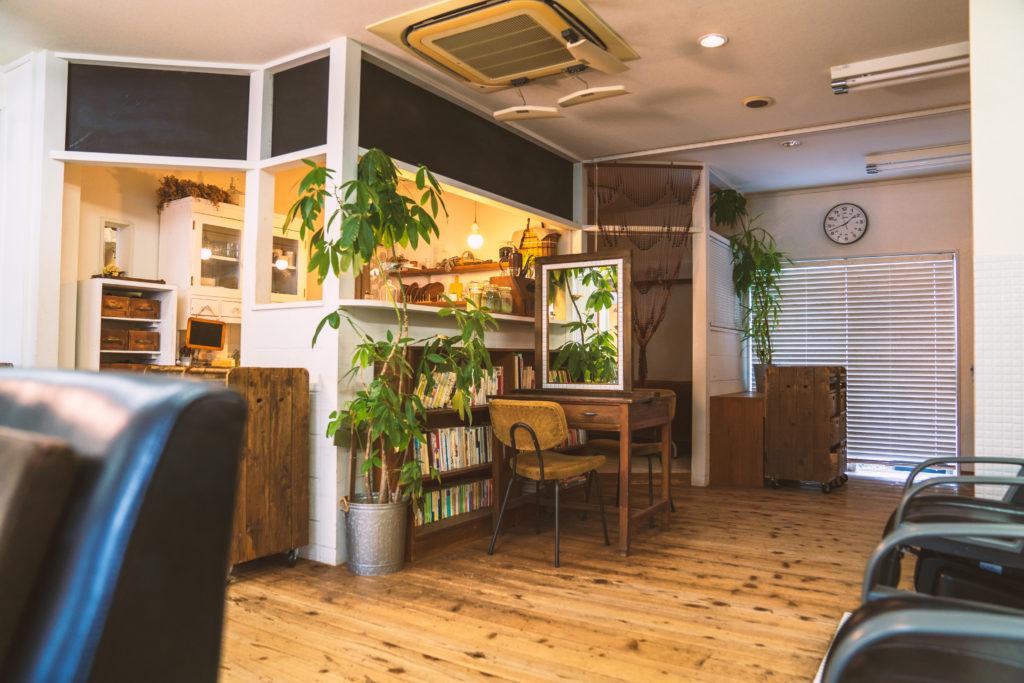 観葉植物が置かれたウッドの床、大きな鏡が付いているテーブルの横には本棚があるオリーブの店内。