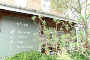 大きな看板に店名やサービスが書かれている、緑に囲まれて落ち着いた雰囲気の美容室オリーブの外観