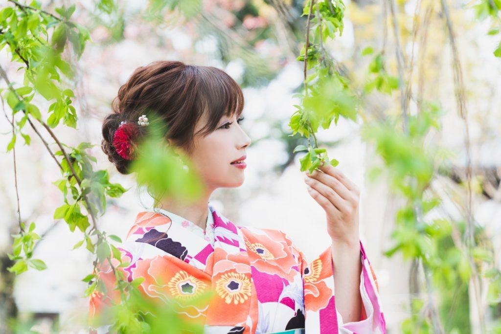 ピンクやオレンジ色の花模様の華やかな着物を着た美しい女性が若い木の葉を持って微笑んでいる、髪はやや下目に一つにまとめられ、赤い大きな花の飾りをつけている。