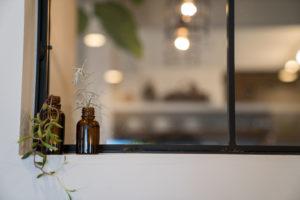 ブラウンの2つの小さな瓶に、観葉植物がささっている美容室ミモザ店内窓際の様子