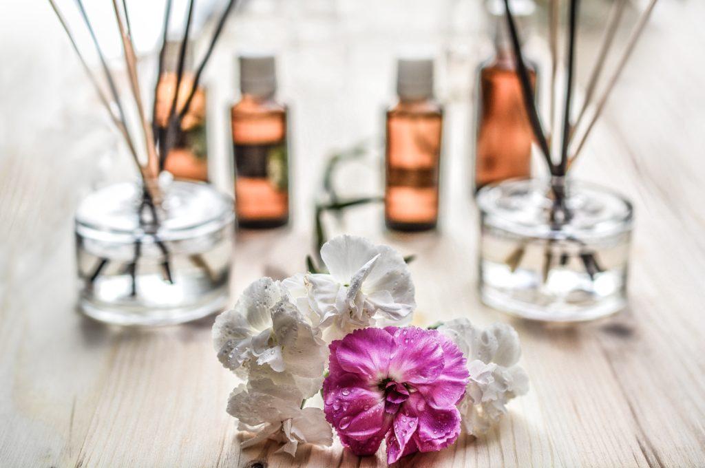 ピンクと白の花のバックにオイルが並んでいる様子