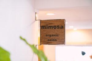 正方形の木にmimosa organic saalonと黒字で書かれた店内サイン