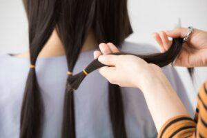 ヘアドネーションをする前に髪を束ねている様子